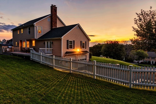 Colonial House with White Picket Fence in Sunset